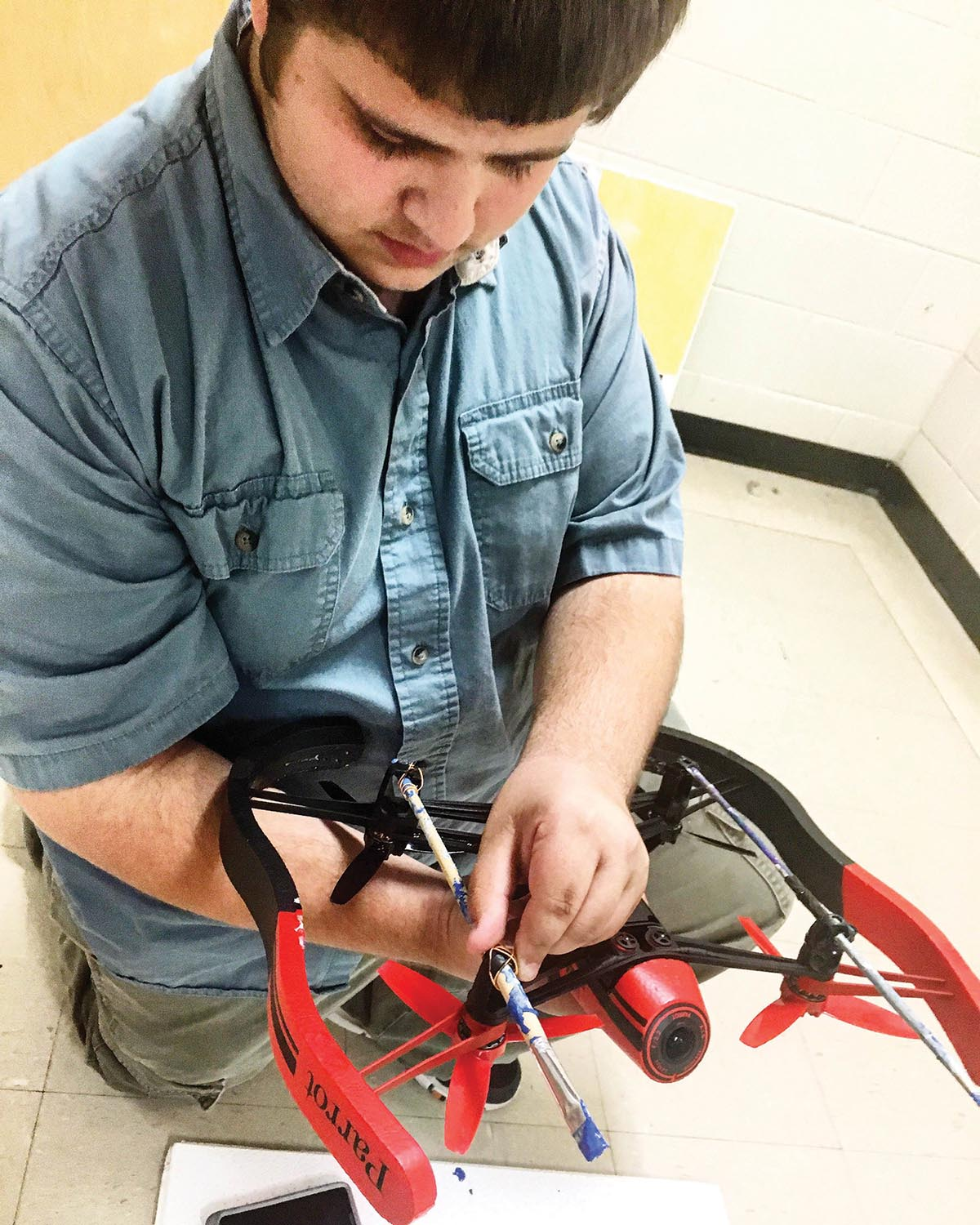 Junior Jesse Byrd modifies a Parrot drone, prepping it for artistic flight. Photograph by Ryan B. Jackson