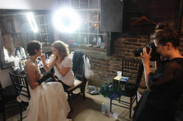 Makeup artist Janelle Wood puts the finishing touches on Kate Tucker while documentary photographer Emily B Hall captures the moment. Photo by Jason Smythe