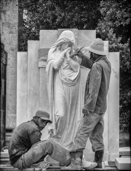 Julia Gary: While on a photography tour of Havana, Cuba I was most anxious to capture images of the exquisite Carrara marble monuments in the Colon Cemetery, even though it was during a time when workmen and artisans were cleaning and restoring the memorials. I photographed the statue of Mary as two craftsmen were carefully cleaning the crevices of the marble when suddenly one artisan looked up as I depressed the shutter, adding depth to the finished image.