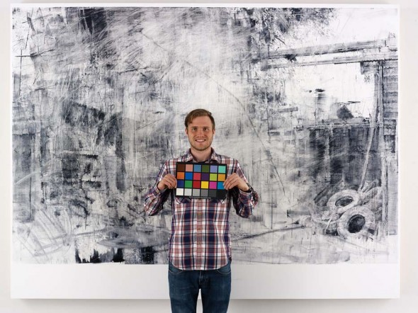 "Damian Stamer standing in front of Patrick Rd. 8, 2013, Oil on panel, 72"" x 95"". Photograph by Max Yawney"