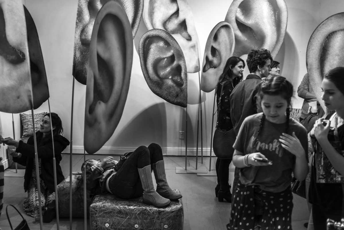 People wander through ears during an art show at the Arcade in downtown Nashville.