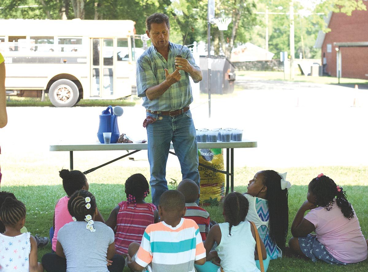 Dan Harrell, from University of Tennessee Agriculture Extension, talks to children at Olivet Day Camp about the importance of a plant's root structure Photograph courtesy of Cheekwood