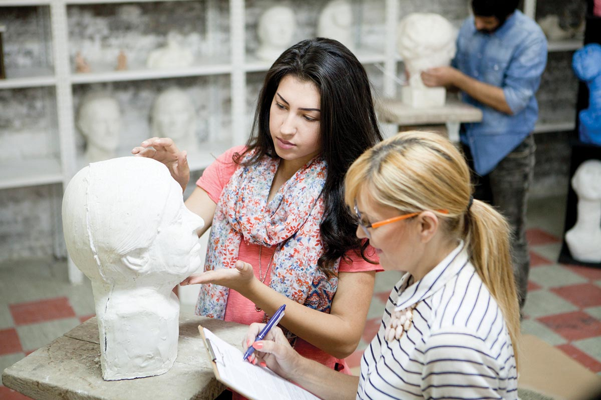 Female student having a sculpting classes, discuss with professor about their work.