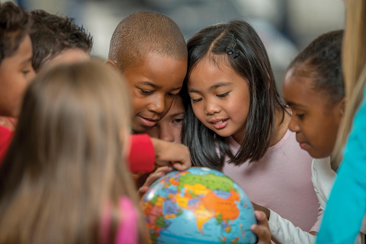 A multi-ethnic group of elementary age students are learning the places of the world by looking at a globe in geography and history class.